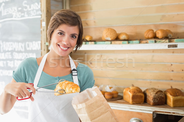 Pretty waitress picking up croissant Stock photo © wavebreak_media