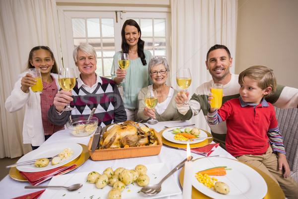 Smiling family toasting to camera during christmas dinner Stock photo © wavebreak_media