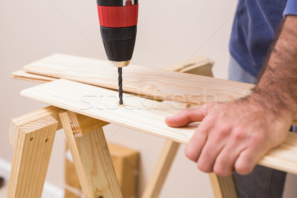 Casual man drilling hole in plank Stock photo © wavebreak_media