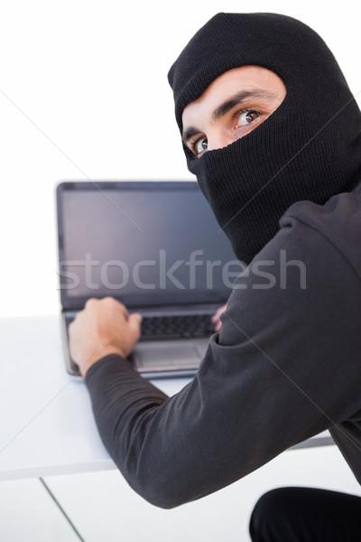 Burglar hacking into laptop while looking at camera Stock photo © wavebreak_media