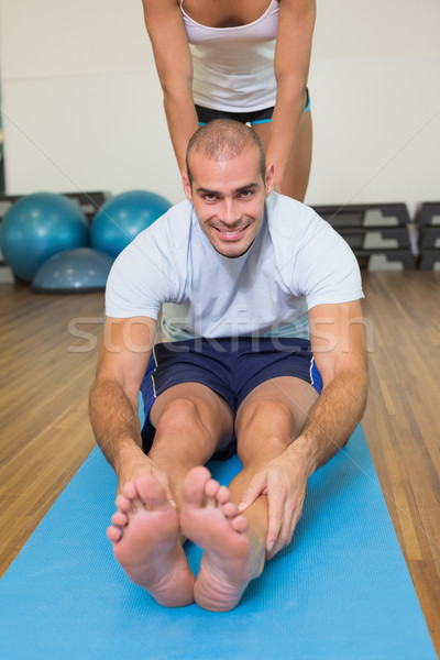Trainer assisting man with stretching exercises at fitness studi Stock photo © wavebreak_media