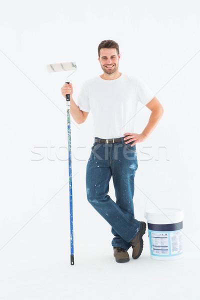 Happy man holding paint roller Stock photo © wavebreak_media