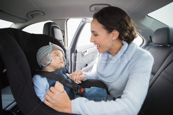 Stock photo: Mother securing her baby in the car seat