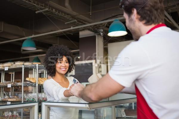 Smiling waiter doing transaction with customer Stock photo © wavebreak_media