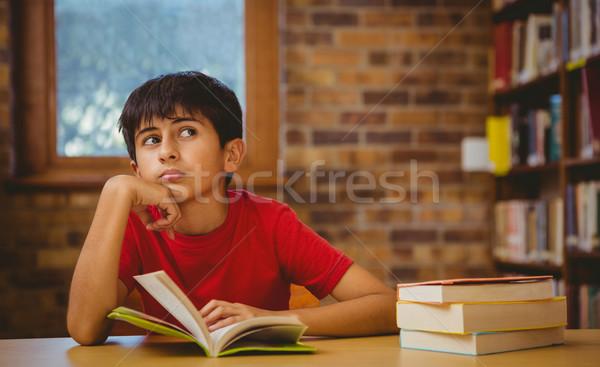 Zamyślony chłopca czytania książki biblioteki mały Zdjęcia stock © wavebreak_media