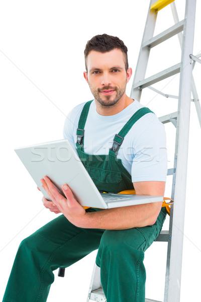 Falegname seduta scala utilizzando il computer portatile bianco computer Foto d'archivio © wavebreak_media