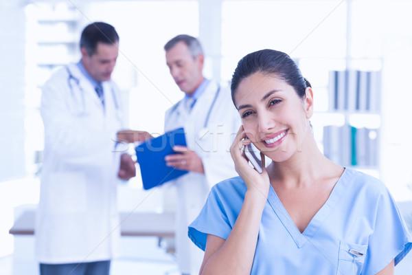 Smiling femal doctor phoning Stock photo © wavebreak_media