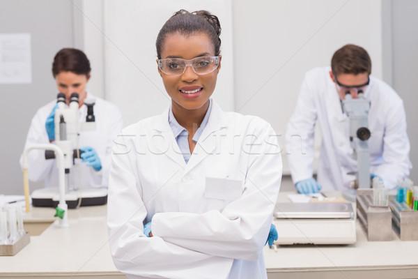 Happy scientist smiling at camera with protective glasses Stock photo © wavebreak_media