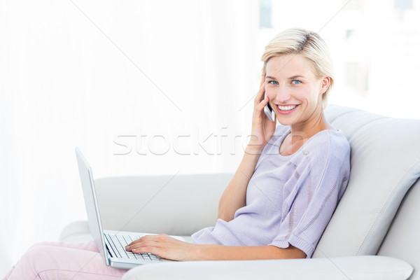 Pretty blonde woman calling on the phone and using her laptop Stock photo © wavebreak_media