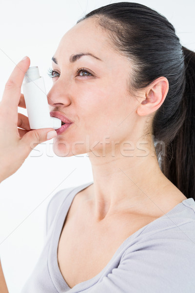 Asthmatic pretty brunette using inhaler  Stock photo © wavebreak_media