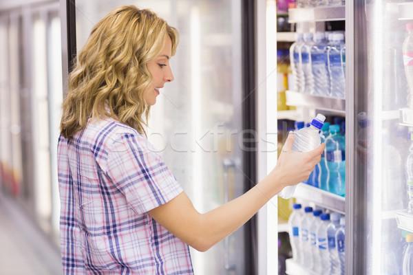 Sorridente mulher loira garrafa de água supermercado negócio Foto stock © wavebreak_media