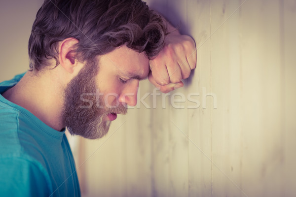 Troubled hipster leaning against wall Stock photo © wavebreak_media