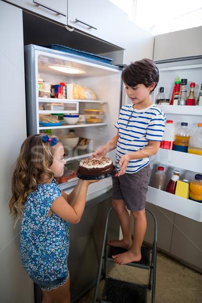 Siblings removing cake from refrigerator in kitchen Stock photo © wavebreak_media