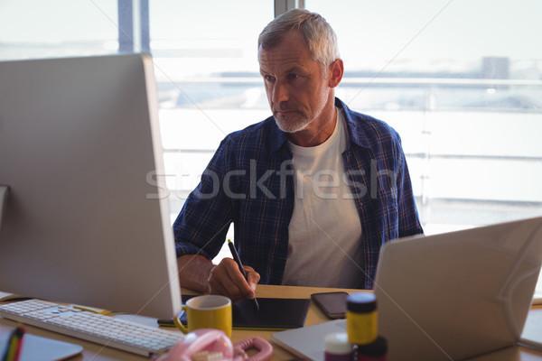 Serious businessman working on digitizer at office desk Stock photo © wavebreak_media
