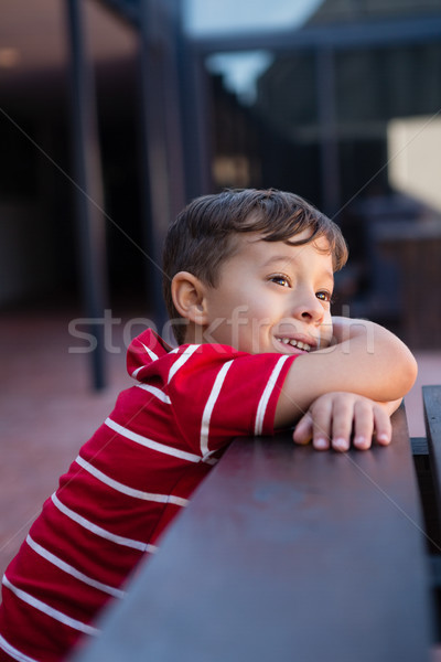 Close up of cute boy looking away while leaning on table Stock photo © wavebreak_media