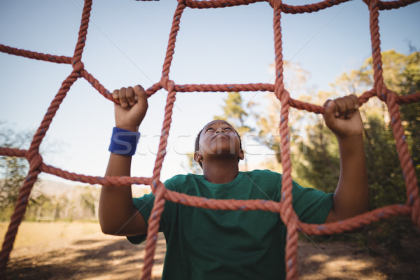 Determined boy climbing a net during obstacle course Stock photo © wavebreak_media