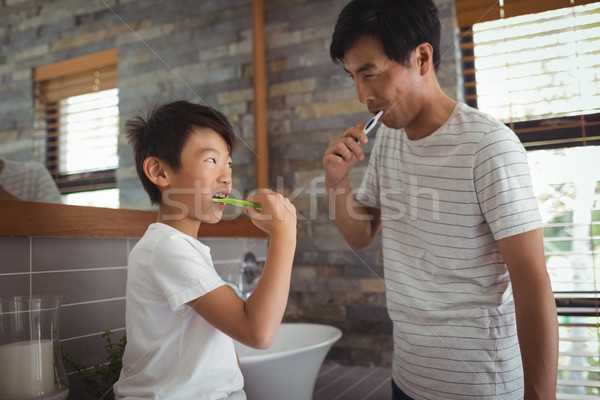 Father and son brushing teeth together in bathroom Stock photo © wavebreak_media