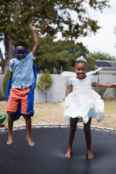 Playful siblings in costumes jumping on trampoline Stock photo © wavebreak_media