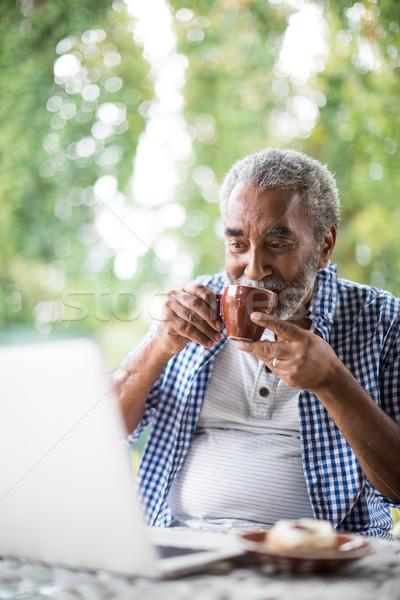 Man having drink while using laptop Stock photo © wavebreak_media