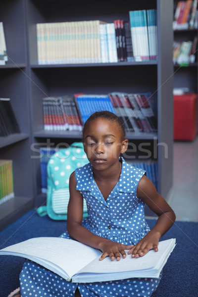 Stock photo: Girl reading braille in library