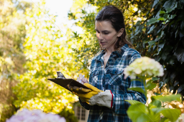 Female gardener writing on clipboard by flowers Stock photo © wavebreak_media