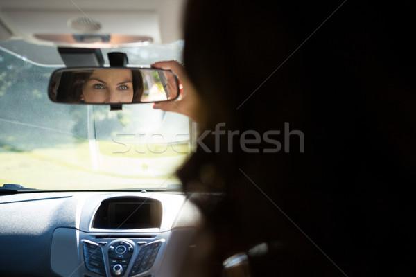 Woman looking into rear view mirror while driving a car Stock photo © wavebreak_media