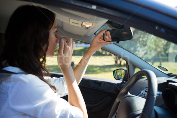 Mulher olhando espelho condução carro Foto stock © wavebreak_media