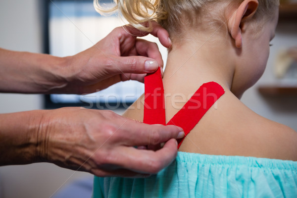 Physiotherapist sticking tape on girl patient Stock photo © wavebreak_media