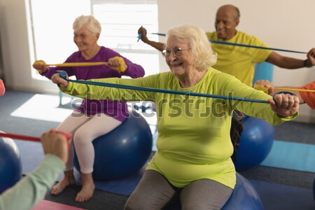 Physiotherapist assisting senior woman in performing stretching exercise with resistance band Stock photo © wavebreak_media