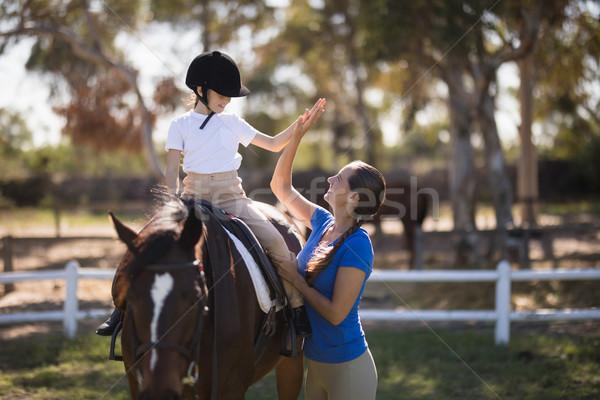 Widok z boku kobieta high five dziewczyna posiedzenia konia Zdjęcia stock © wavebreak_media