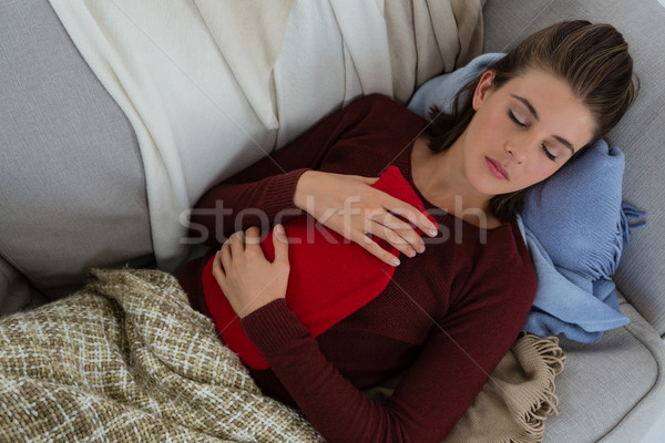 High angle view of woman holding hot water bottle while sleeping on sofa at home Stock photo © wavebreak_media