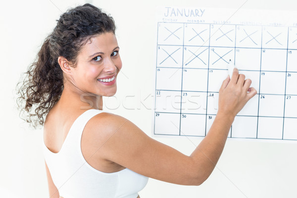Happy pregnant woman marking off dates on calendar Stock photo © wavebreak_media