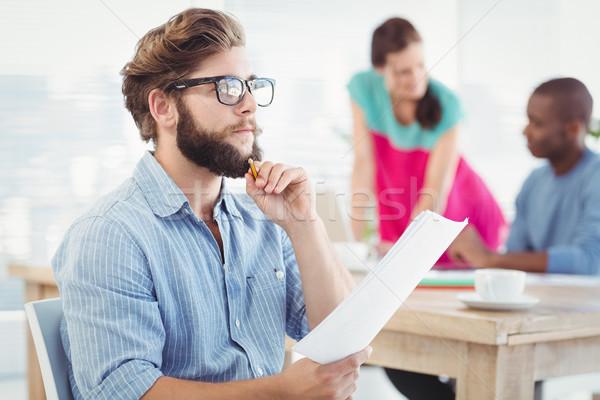 Thoughtful man wearing eyeglasses and holding paper  Stock photo © wavebreak_media