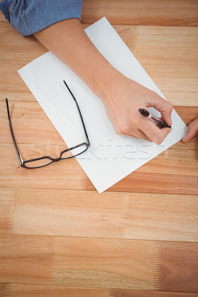 Hipster writing in paper at desk Stock photo © wavebreak_media