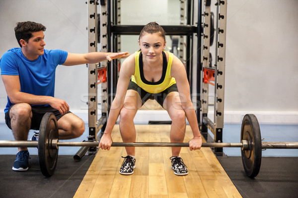 Woman lifting barbell and weights with trainer watching Stock photo © wavebreak_media