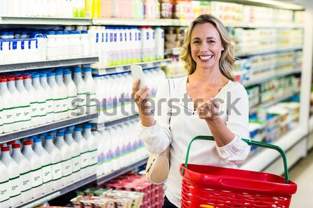 Smiling woman with red basket buying milk Stock photo © wavebreak_media