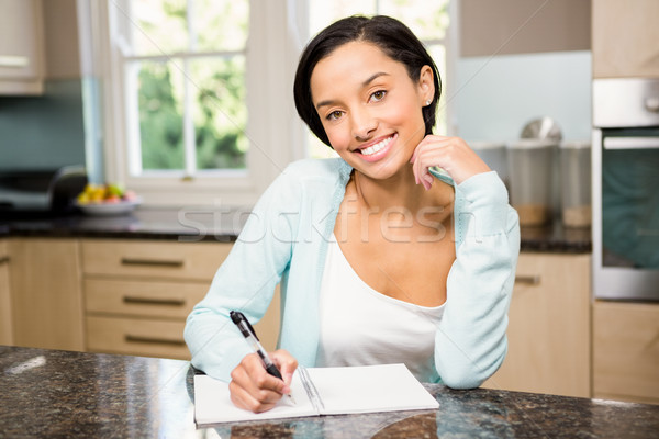 Smiling brunette writing on note pad Stock photo © wavebreak_media