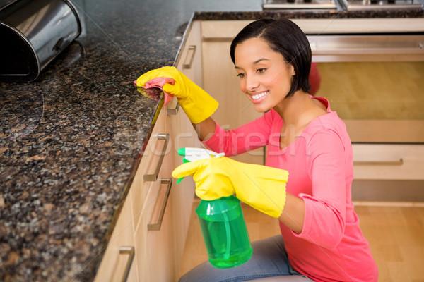 Smiling brunette cleaning kitchen counter Stock photo © wavebreak_media
