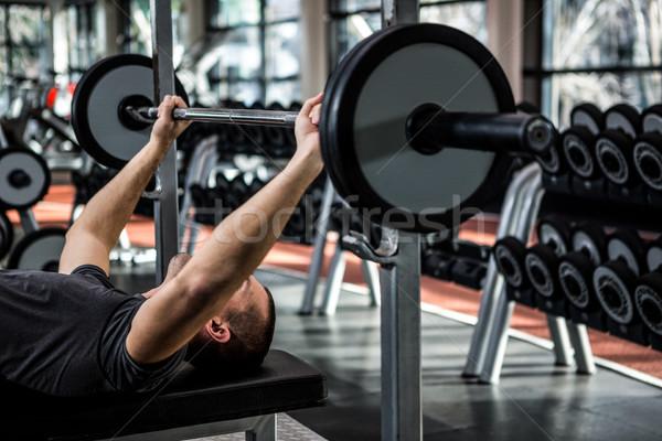 Muscular man lifting barebell while lying on bench Stock photo © wavebreak_media