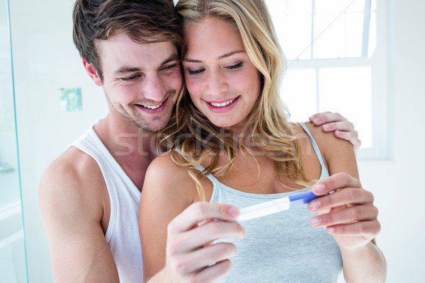 Happy couple looking at pregnancy test Stock photo © wavebreak_media