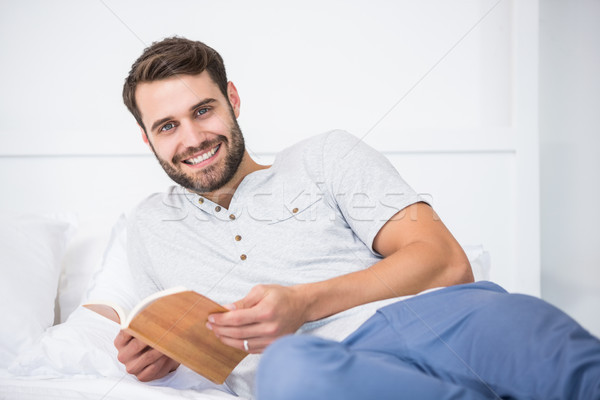 Adam kitap yatak ev gülen Stok fotoğraf © wavebreak_media