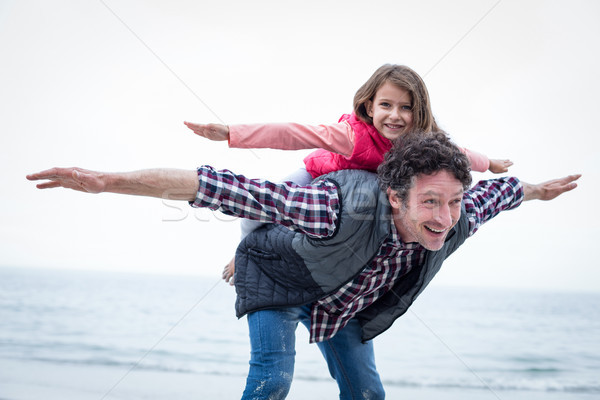 Happy father carrying daughter on back at sea shore Stock photo © wavebreak_media
