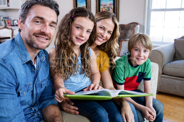 Portrait of happy family sitting on sofa with photo album Stock photo © wavebreak_media