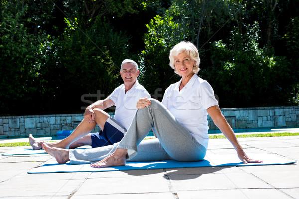 Smiling couple on exercise mat at poolside Stock photo © wavebreak_media