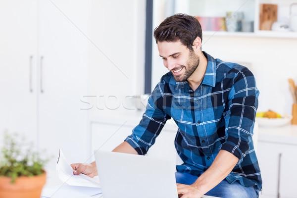 Jonge man betalen Bill online laptop keuken Stockfoto © wavebreak_media