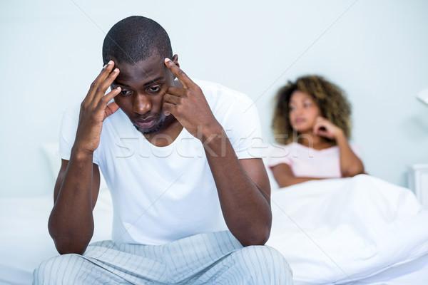 Tensed man sitting on bed in bedroom Stock photo © wavebreak_media