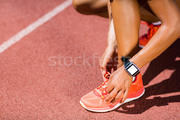 Female athlete tying her shoe laces on running track Stock photo © wavebreak_media