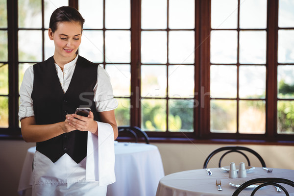 Waitress using mobile phone Stock photo © wavebreak_media