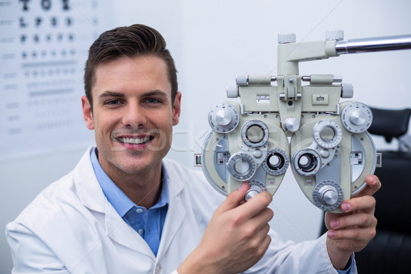 Smiling optometrist adjusting phoropter Stock photo © wavebreak_media