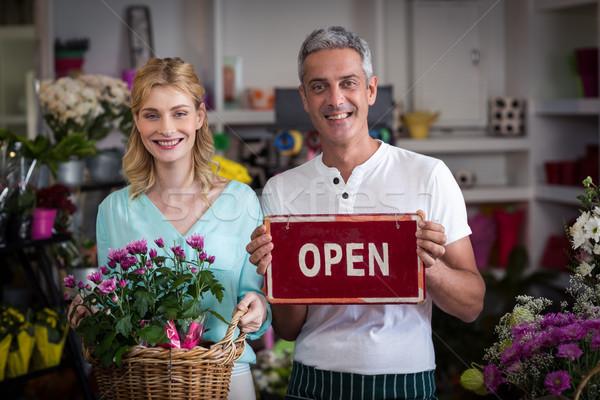 Florists holding open sign placard and flower basket in flower shop Stock photo © wavebreak_media